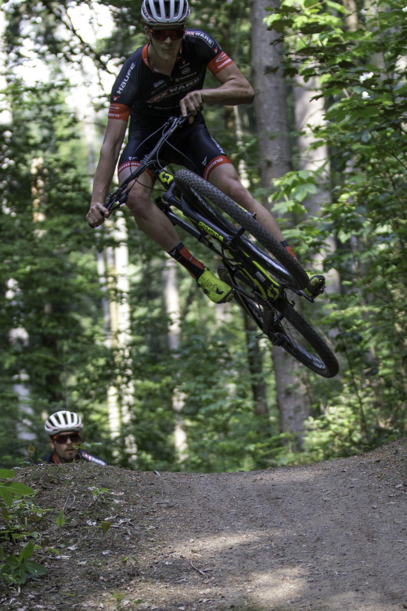 Ein Mountainbiker springt über einen Hügel