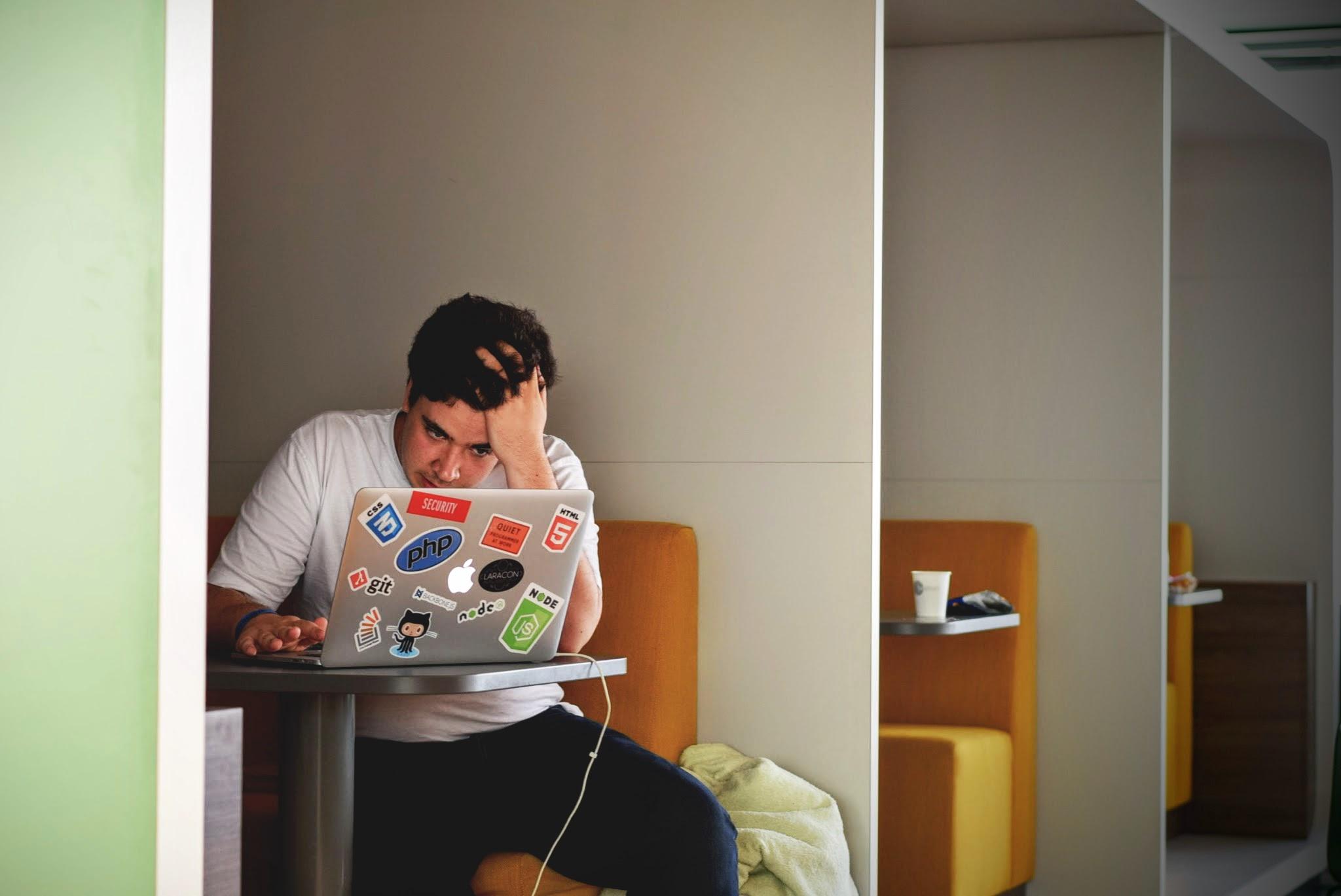 Informatiker sitzt an einem Laptop mit Aufklebern verschiedener IT-Projekte