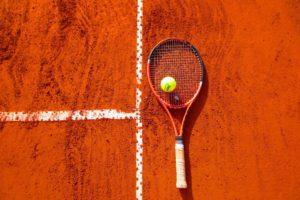 Tennisschläger liegt auf Sandplatz